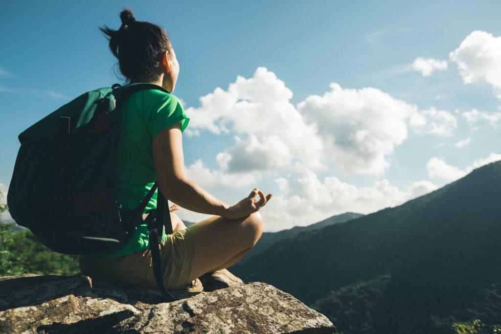 Hiker meditation on mountain top