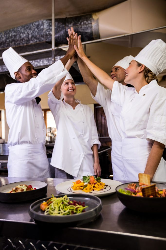 Group of chefs formig hands stack in kitchen at hotel