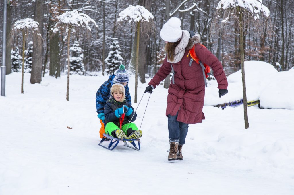 Winter family playing outdoor in the park.